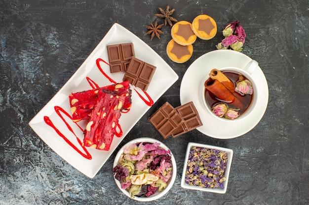 Вид сверху шоколадных конфет на белой тарелке с травяным чаем и сухими цветами и печеньем на серой земле