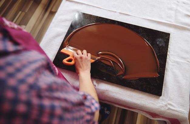 大理石のテーブルにケーキスクレーバーを保持し、溶かしたチョコレートの塊を冷却するショコラティエの上面図。閉じる