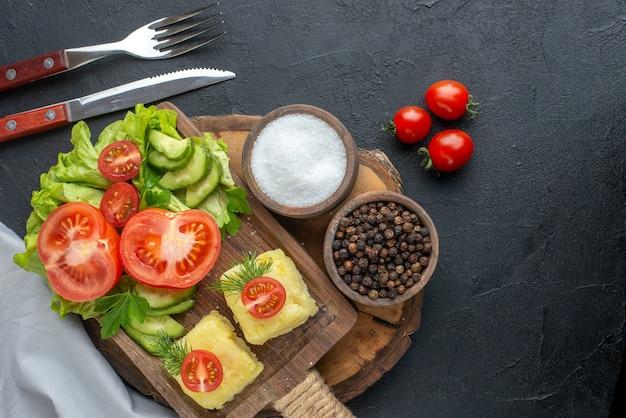 まな板に刻んだ新鮮な野菜チーズと黒い表面にセットされたスパイスカトラリーの上面図