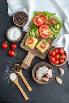 ボウルのまな板に刻んだ新鮮な野菜全体と黒い表面の白いタオルにスパイスの上面図