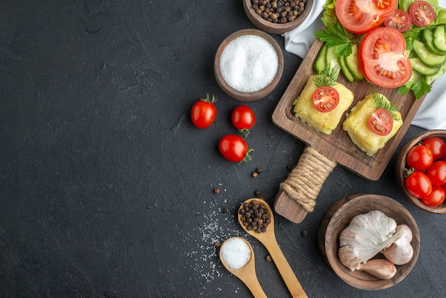 ボウルのまな板に刻んだ新鮮な野菜全体と黒い表面の左側にある白いタオルのスパイスの上面図