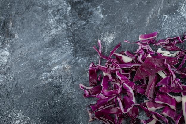 Вид сверху нарезанной фиолетовой капусты на сером фоне.