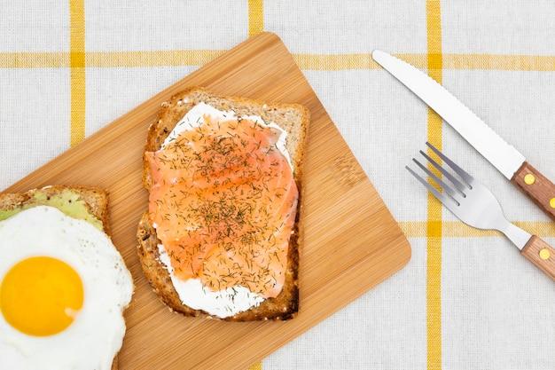 Вид сверху разделочную доску с тостами и яйцом на вершине