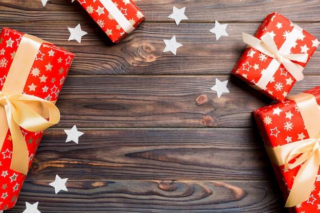 木製の背景にギフトボックスと星で作られたクリスマス背景の平面図です。コピースペースで新年の休日の概念