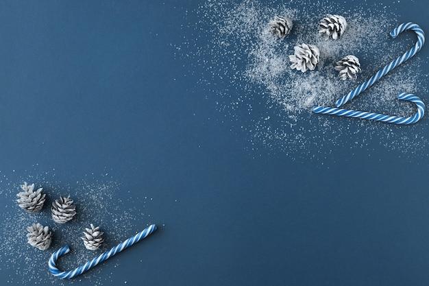 雪に覆われたモミの木の円錐形、クラシックな青い背景の上の青いキャンディケインの装飾のクリスマスの構成の上面図。クリスマス、冬、新年のコンセプト。フラットレイとコピースペース