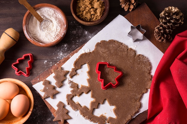Вид сверху на тесто для рождественского печенья с формами елки