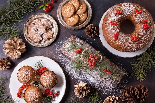 Вид сверху рождественских десертов с красными ягодами и сосновыми шишками