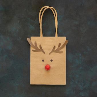 Вид сверху на рождественский подарочный пакет с украшением из оленей