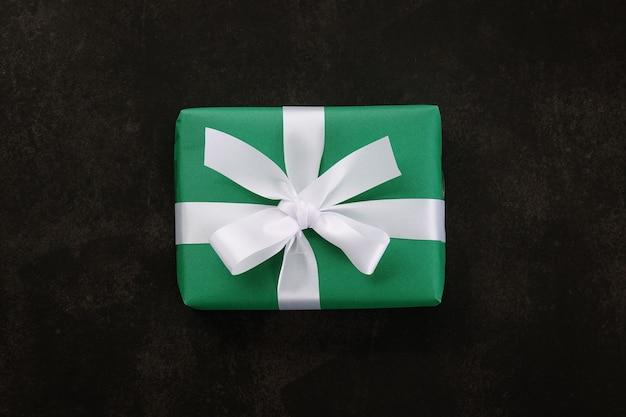 Вид сверху рождественской подарочной коробки, обернутой зеленой бумагой и белой лентой на фоне гранж.