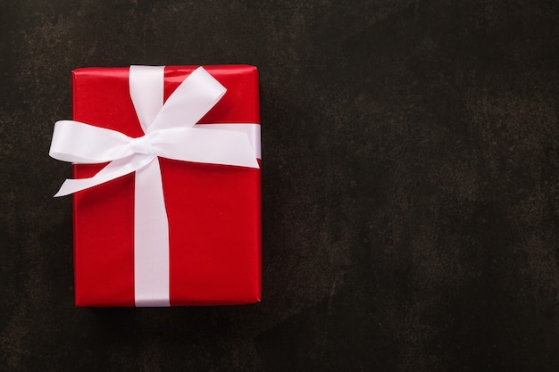 Вид сверху рождественской подарочной коробки, обернутой красной бумагой и белой лентой на фоне гранж.