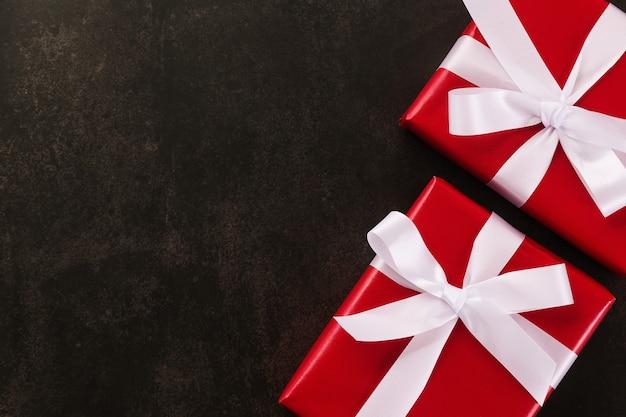 Вид сверху рождественских подарочных коробок, обернутых красной бумагой и белой лентой на фоне гранж.