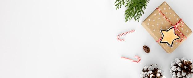 Вид сверху рождественского подарка с сосновыми шишками, леденцами