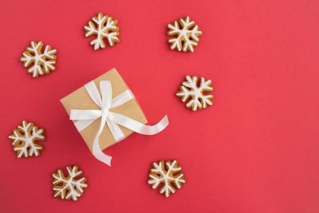Вид сверху рождественского подарка с белым бантом и снежинками из пряников