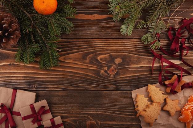 어두운 나무 보드에 크리스마스 진저 쿠키, 선물, 귤 및 크리스마스 트리 분기의 상위 뷰.