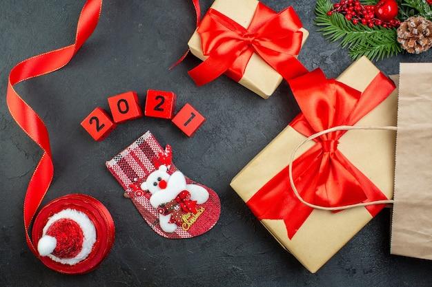 Вид сверху на рождественское настроение с красивыми подарками, еловые ветки, хвойные шишки, красная ленточка и цифры, новогодний носок шляпы санта-клауса на темном фоне