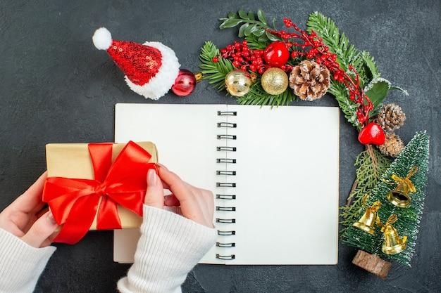 Вид сверху на рождественское настроение с еловыми ветками шляпа санта-клауса, держащая подарочную коробку с красной лентой на темном фоне