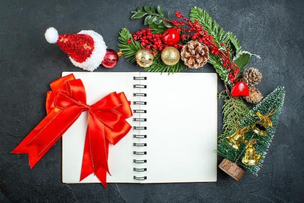 어두운 배경에 노트북에 전나무 가지 산타 클로스 모자 크리스마스 트리 레드 리본 크리스마스 분위기의 상위 뷰