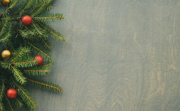 Вид сверху рождественской сосны с красными и золотыми шарами на черном деревянном фоне