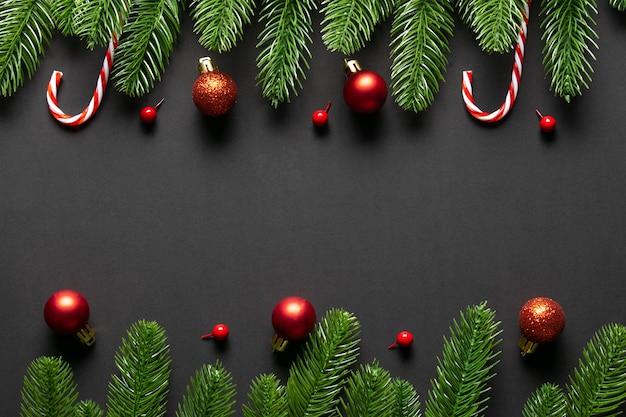 Вид сверху рождественских красных шаров с еловыми ветками на черном деревянном фоне. скопируйте пространство.