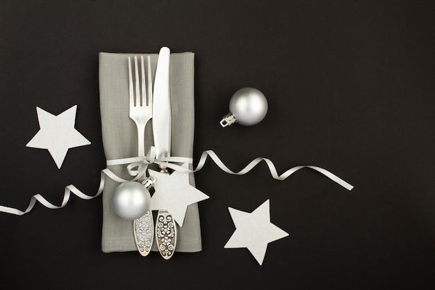 コピースペースと暗い背景の上のクリスマステーブル設定の上面図