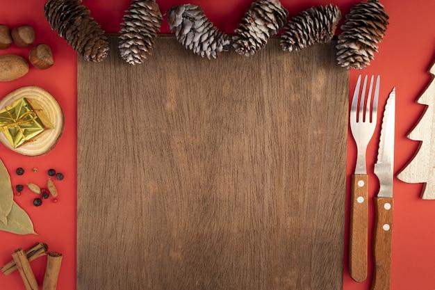 Вид сверху сервировки рождественского стола со столовыми приборами и сосновыми шишками