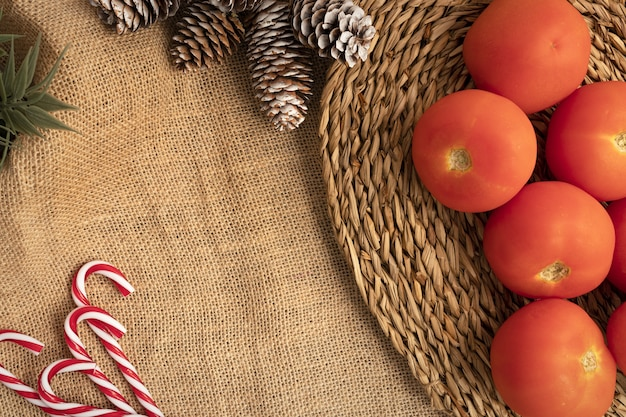 Вид сверху на сервировку рождественского стола с помидорами, леденцами и сосновыми шишками