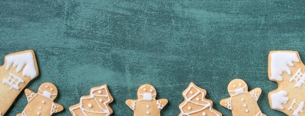 Вид сверху на рождественскую елку и снежинки с маской пряничного человечка на зеленом фоне стола.