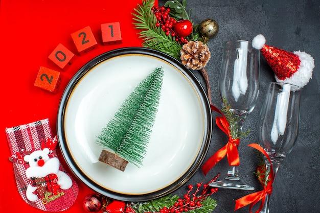 Вид сверху елки на тарелке, стеклянные бокалы, рождественский носок на темном фоне