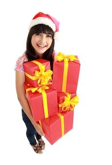 Взгляд сверху женщины рождества держа подарки нося шляпу санты. стоя в полном теле изолированы. улыбающиеся женщина портрет красивой азиатской модели.