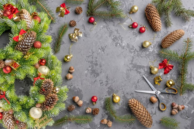 Вид сверху рождественский венок с ели, сосновые шишки, шарики и ленты на бетонной поверхности