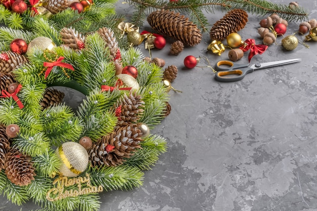 Вид сверху рождественский венок с ели, сосновые шишки, шарики, ленты и желуди на бетонной поверхности