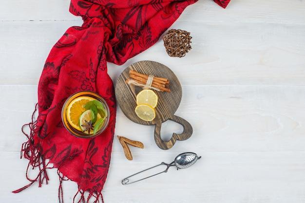 ハーブティーと木の板にシナモンと柑橘系の果物の上面図