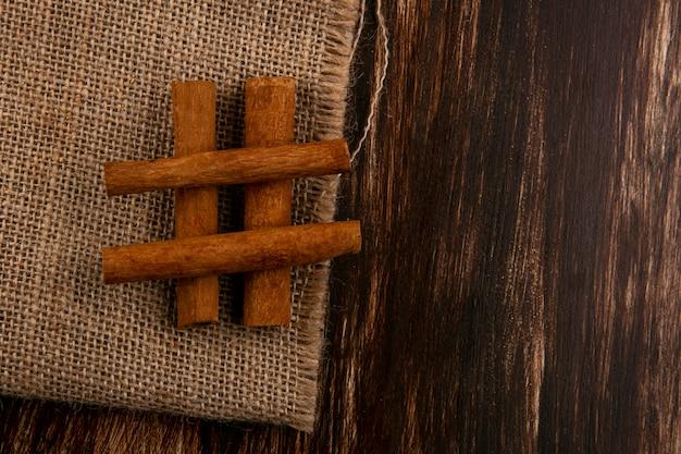 コピースペースを持つ木製の背景に荒布を着たシナモンのトップビュー
