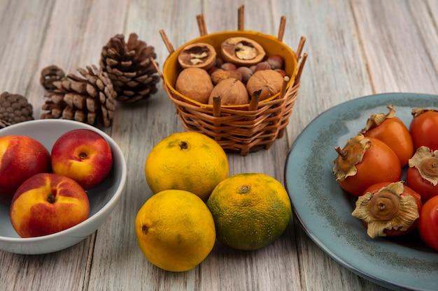 灰色の木の表面のバケツにナッツとボウルに桃とプレートに柿と柑橘系の果物みかんの上面図