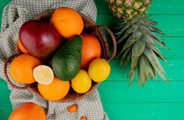 Вид сверху цитрусовых как манго оранжевый лимон авокадо в корзине с ананасом на зеленом фоне