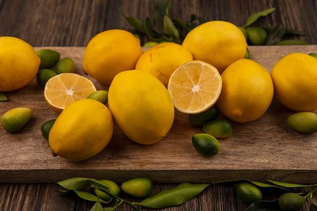 Вид сверху цитрусовых, таких как кинканы и лимоны, на деревянной кухонной доске на деревянном фоне