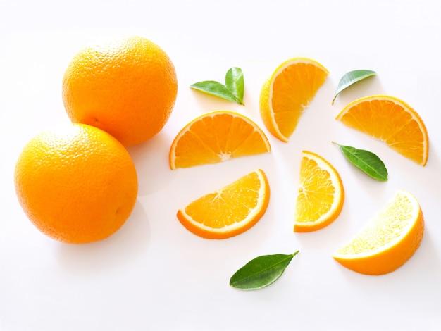 감귤 오렌지 조각의 상위 뷰 흰색 표면에 고립 된 녹색 잎 과일을 슬라이스.