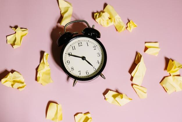 ピンクの背景にしわくちゃの黄色の付箋と古典的な目覚まし時計の上面図