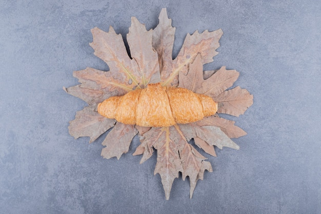 Вид сверху классический французский круассан на сухих листьях