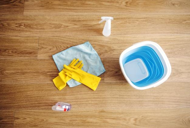 Вид сверху чистящих средств. есть резиновые перчатки, волшебная ткань и моющие средства.