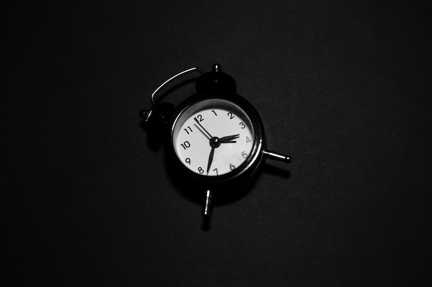 Вид сверху часов на черной поверхности.
