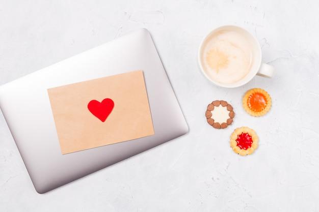 クラフトエンベロープと赤いハート、一杯のコーヒーと来るクッキーと閉じたラップトップの平面図です。デスクトップ。