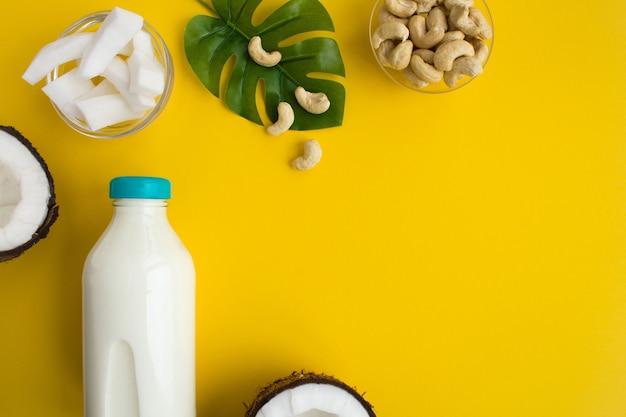 ガラス瓶の中のココナッツミルクと黄色のカシューナッツの上面図 Premium写真
