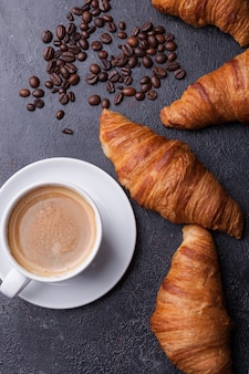 コーヒーとクロワッサンとコーヒー豆の上面図。デリカスコーヒー。