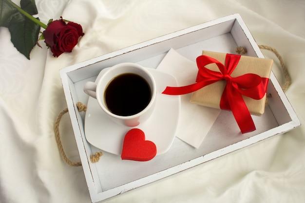 Вид сверху кофе и подарочной коробки на белом деревянном подносе в постели