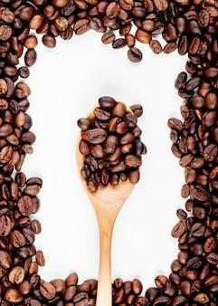 Вид сверху кофейных зерен в деревянной ложкой на белом фоне