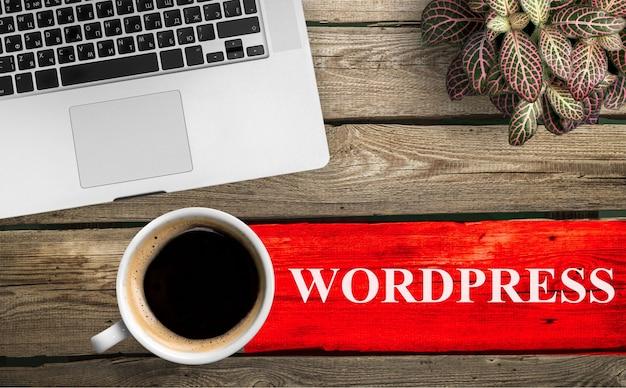 Вид сверху кофейной чашки и клавиатуры с надписью wordpress на столе