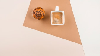Top view of coffee cup and muffins on colored background