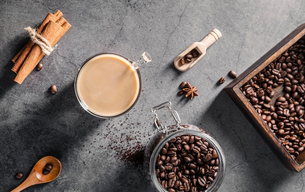 Вид сверху на кофейную чашку с палочками корицы и банку