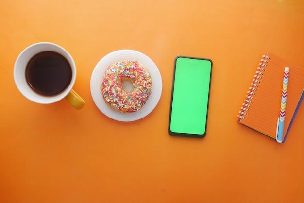 Вид сверху блокнота с кофе и пончиками на оранжевом фоне